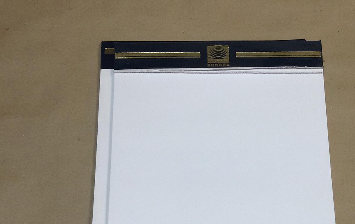 Нужен нестандартный блокнот? Блокнот со склейным корешком, обтянутым искусственной кожей, формата 210х148; блок 60 полос, непечатный, бумага офсетная 100 гр.м2, отрывная перфорация, склейка по короткой стороне, 2 скобы, ручная обклейка корешка, тиснение фольгой.